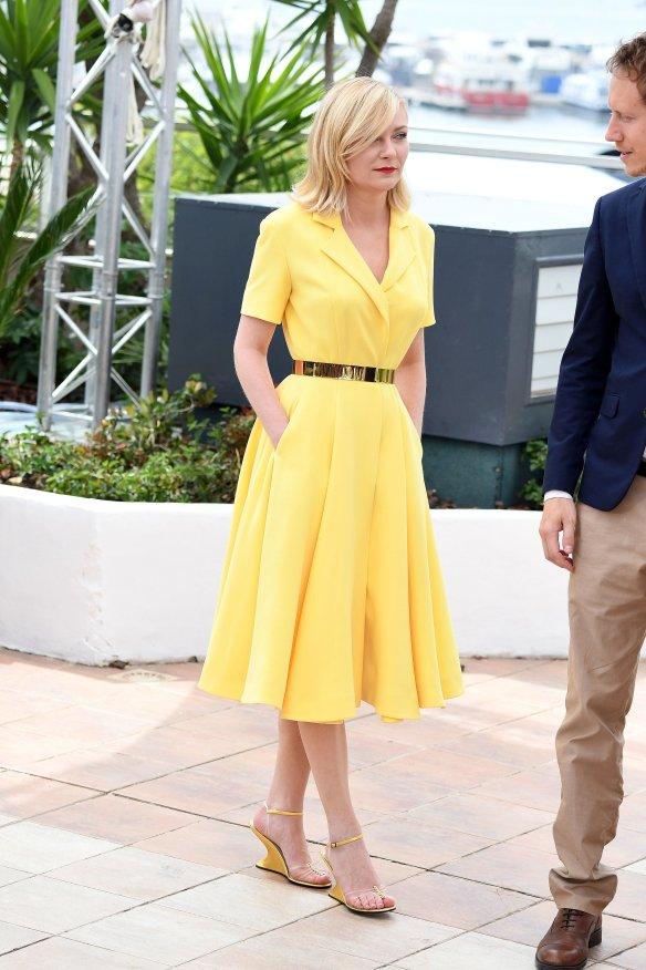 el blog ana suero-Alfombra roja Festival Cannes 2016-Kirsten Dunst Vestido Dior midi amarillo cinturon metalizado